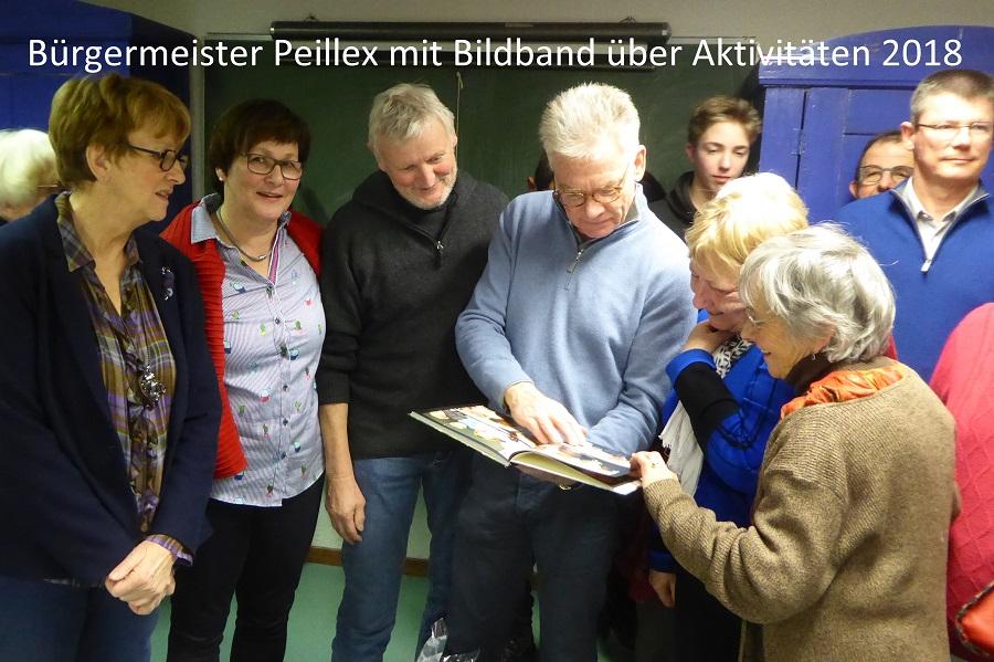 Bürgermeister Peillex betrachtet den Bildband mit den Partnerschaftsaktivitäten 2018, den das französische Komitee geschenkt bekommen hat.