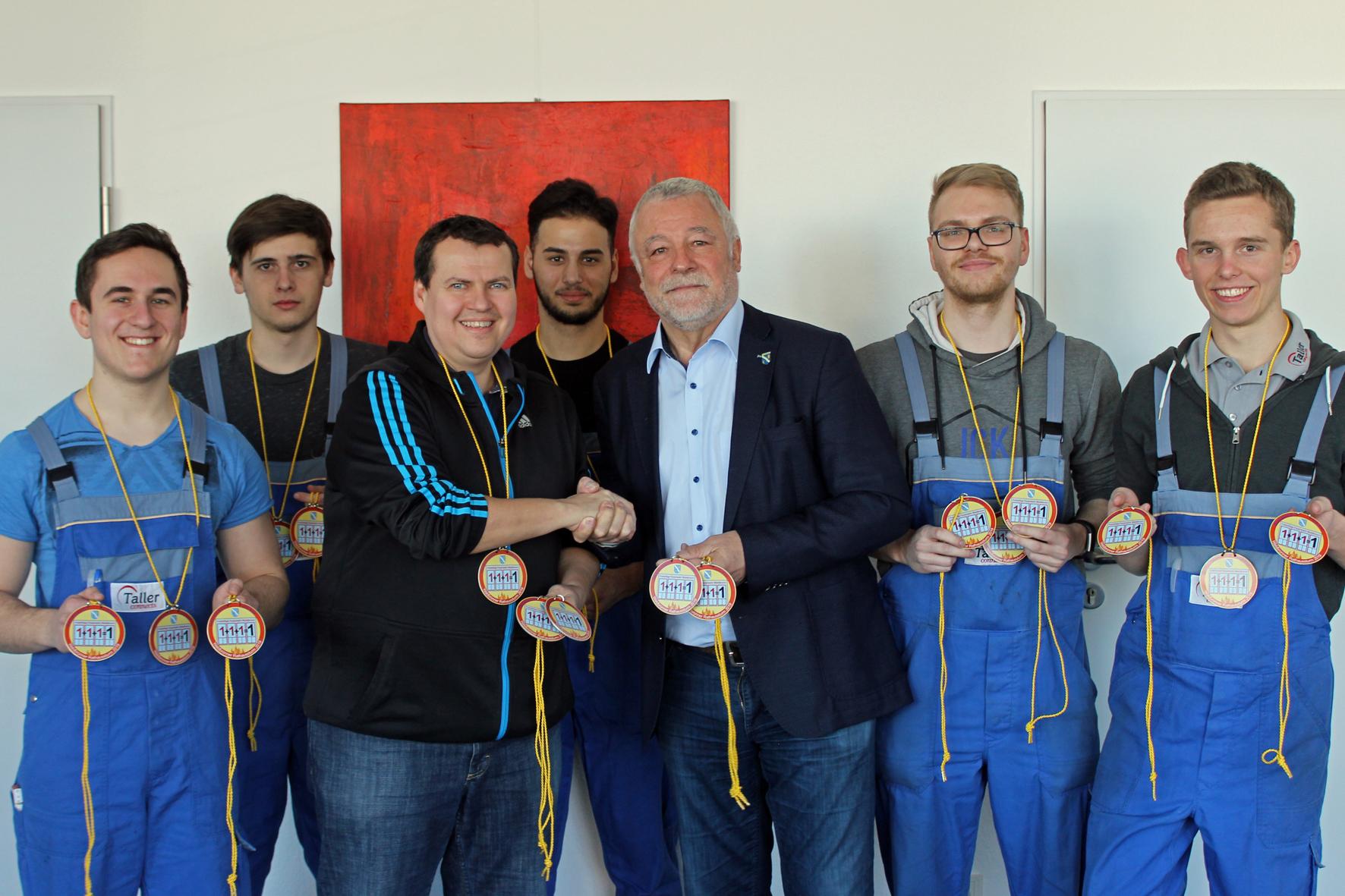 Auszubildende der Firma Taller übergeben gemeinsam mit Ausbildungsleiter Martin Becker die neuen Rathausorden an Bürgermeister Franz Masino.