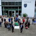 Die Scheckübergabe fand vor dem Rathaus statt. 16 Vereine profitieren von der Spende.  Bild: Agilent