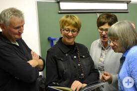 Achim Doster, Véronique Fourmon, Felicitas Naß und Marie-Agnes Laurence (von links) betrachten den Bildband über die Partnerschaftsaktivitäten 2017