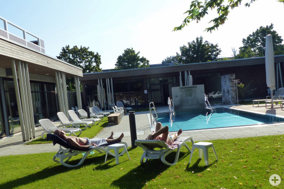 """Zwei Badegäste genießen im Saunagarten der Albtherme Waldbronn die Morgensonne. Da könnte man """"Corona"""" fast vergessen. Bild: Kurverwaltung Waldbronn"""